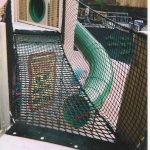 A rope bridge leading to a slide.
