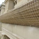 Facade netting uses to layers of netting to catch , hold and secure architectural details on historic building until repairs can be made.